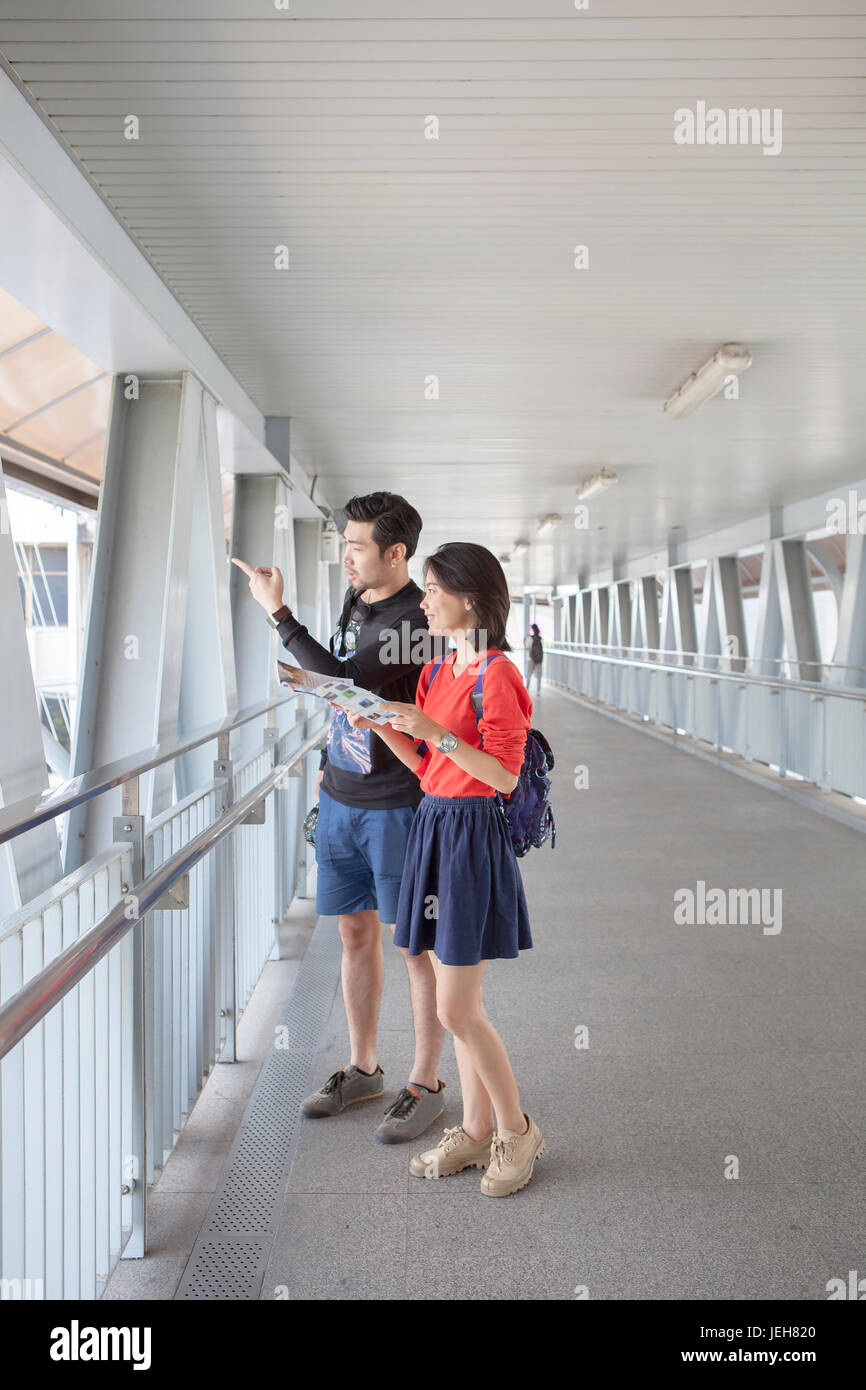 asian younger man and woman looking to traveling destination guide book  in hand - Stock Image