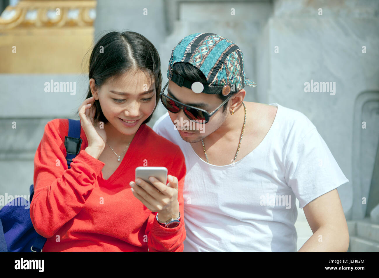 couples of asian younger man and woman looking to smart phone in traveling destination - Stock Image