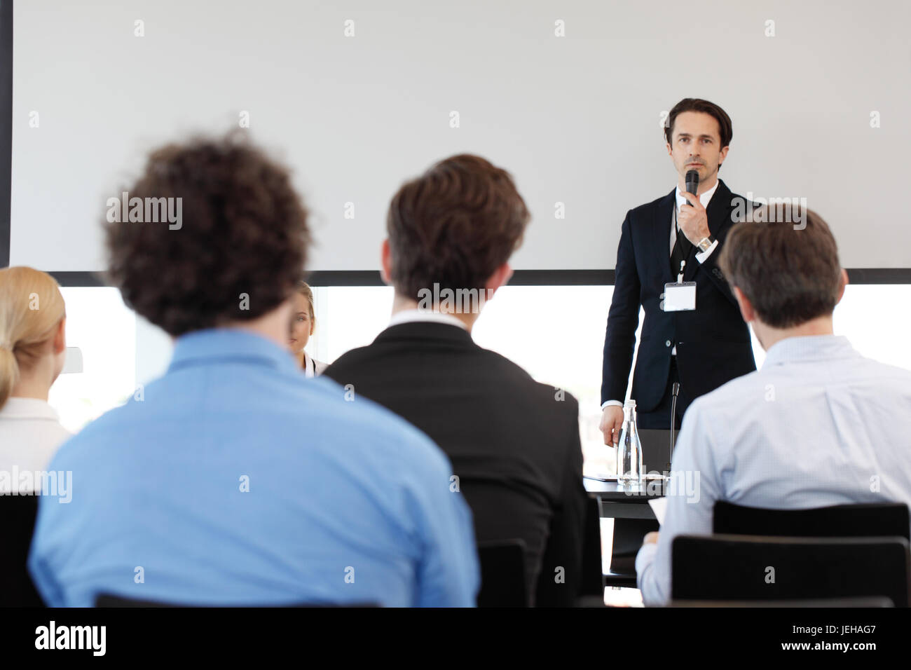 Speaker at business conference near white screen and audience - Stock Image