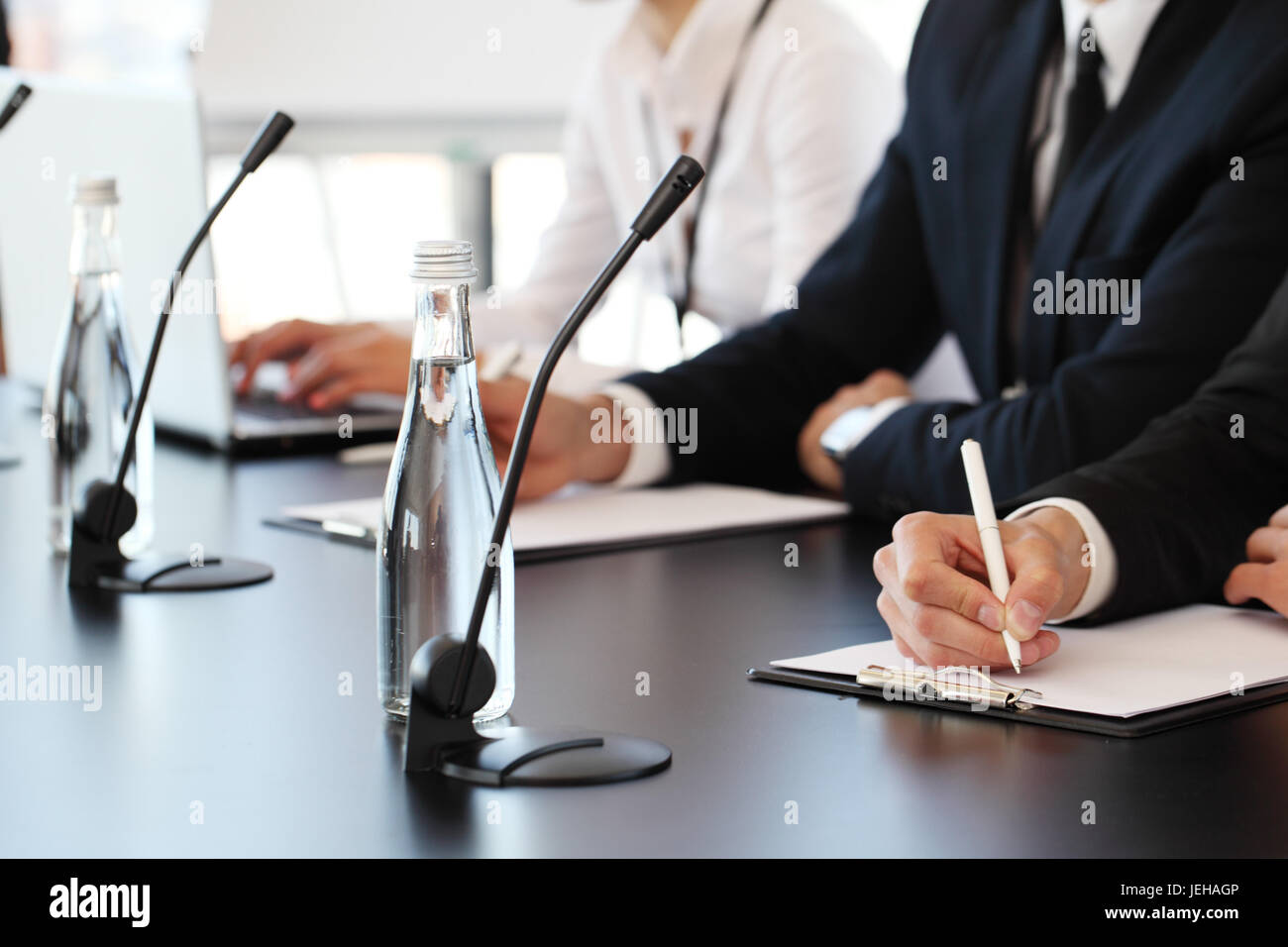 Group of speakers at business meeting at the table with microphones - Stock Image