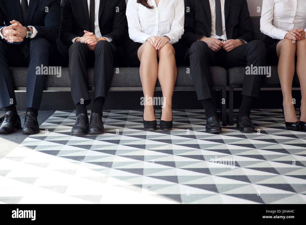 People waiting for job interview sitting on chairs in a row - Stock Image