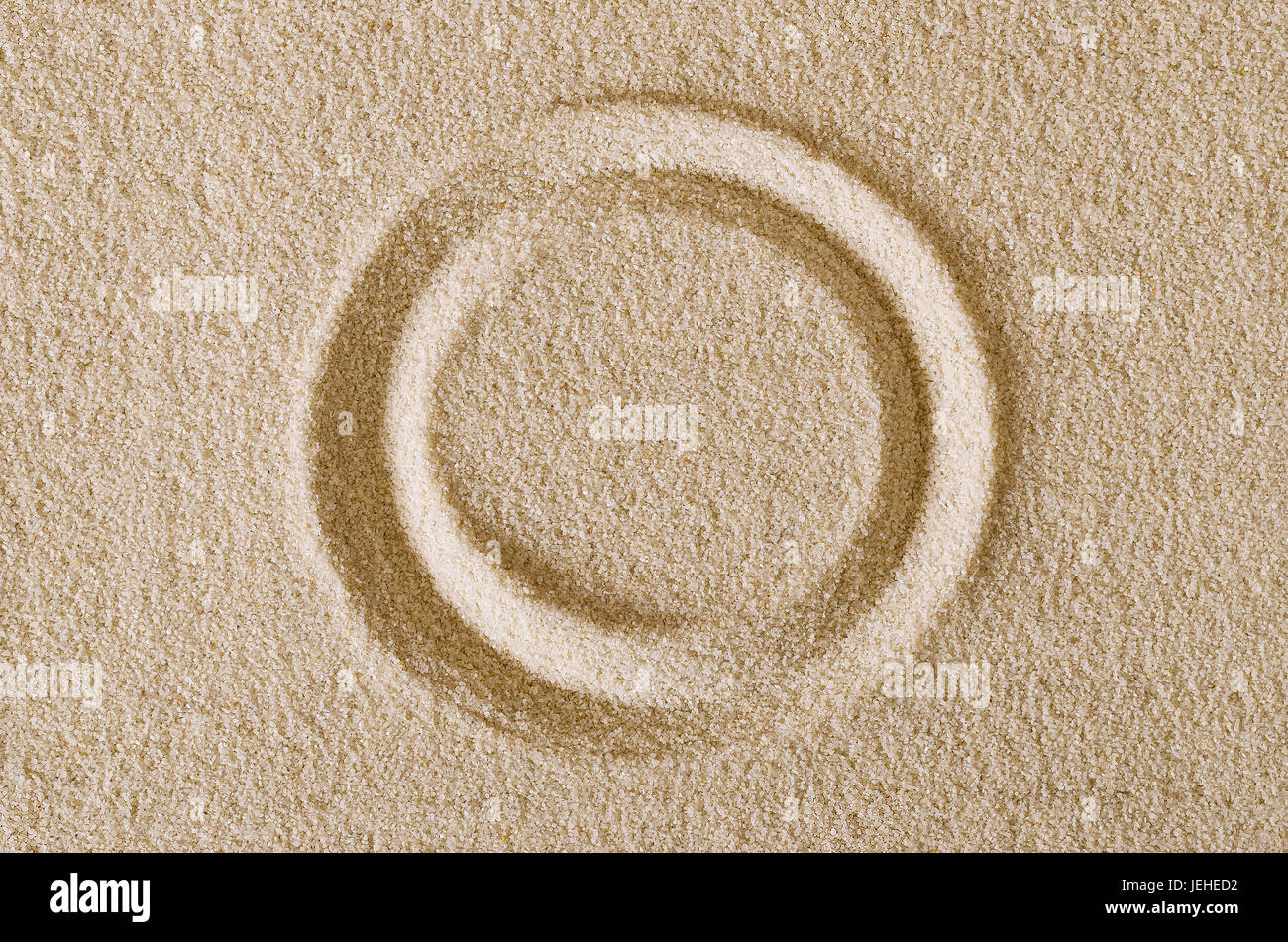 Circle shape imprint in sand surface. A closed curve, a ring or a disc in a rectangular flat sand area. Pictogram - Stock Image