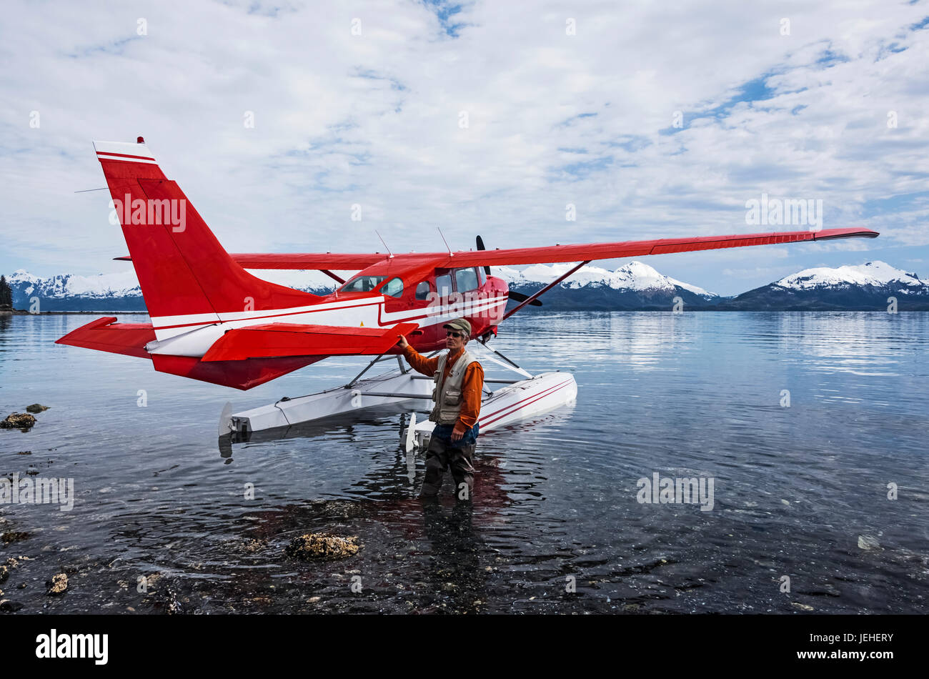Man standing next to a Cessna 206 float plane in Hobo Bay, Port Wells, Prince William Sound, Southcentral Alaska, - Stock Image