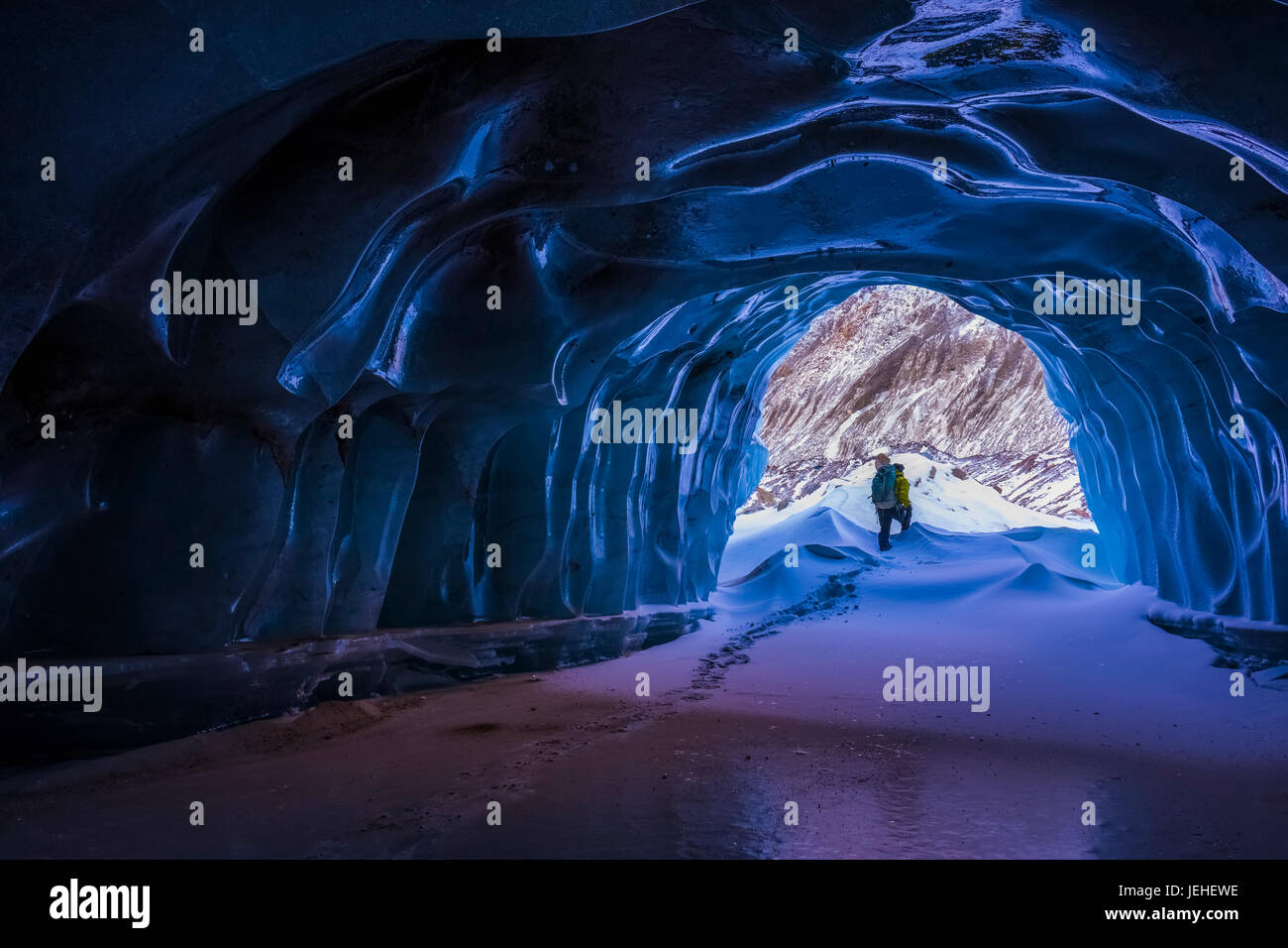 A hiker exits a small ice cave while exploring the terminal moraine of Black Rapids Glacier in the winter; Alaska, - Stock Image