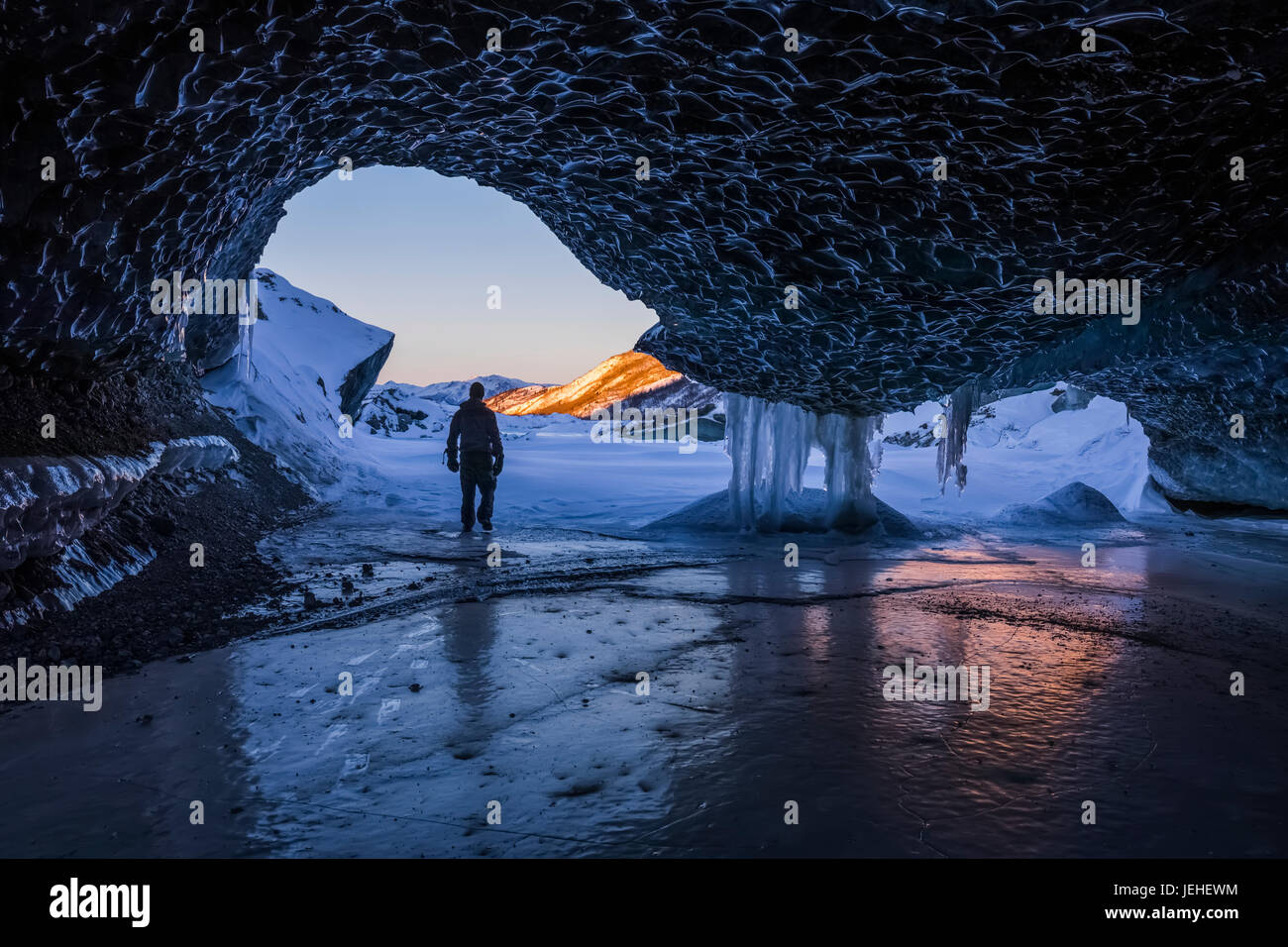 A man walks out the entrance of an ice tunnel at the terminus of Canwell Glacier in the Alaska Range in mid-winter; - Stock Image