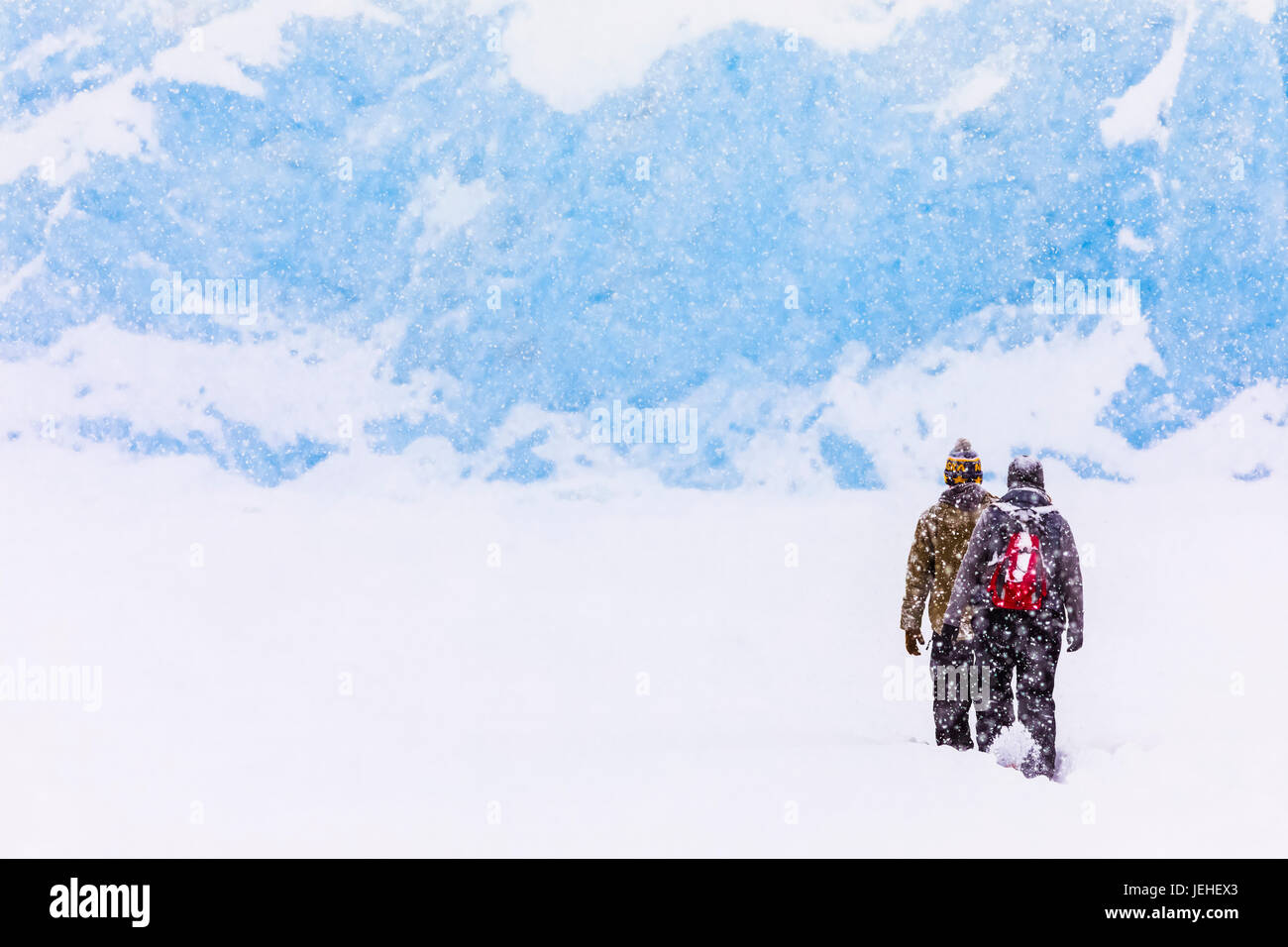 A couple snowshoes across Portage Lake during a heavy snowfall in winter to see the terminus of Portage Glacier, - Stock Image