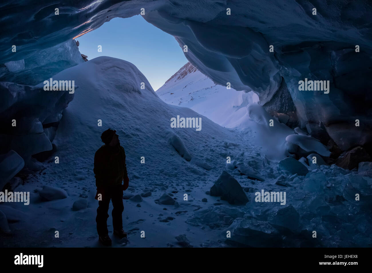 A silhouetted man stands inside the entrance of an ice cave within Augustana Glacier in the Alaska Range in the - Stock Image