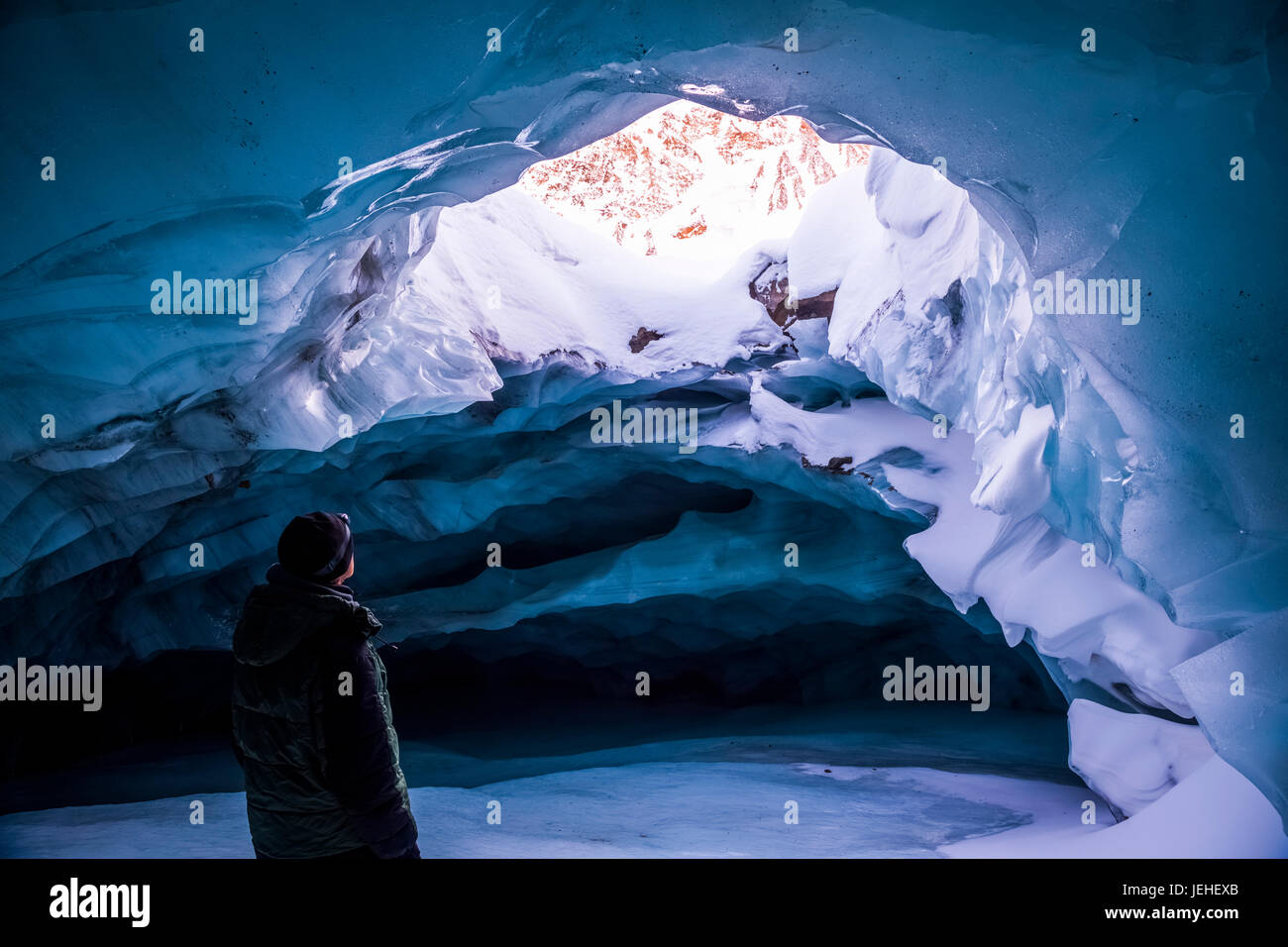 A man looks out an opening in the ceiling of an ice cave within Augustana Glacier in the winter, Alaska Range, Interior - Stock Image