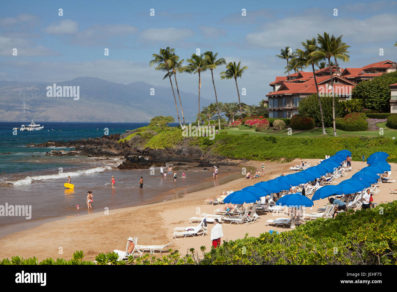 Beach umbrellas on Polo Beach and a snorkel boat off the shore; Wailea, Maui, Hawaii, United States of America - Stock Image