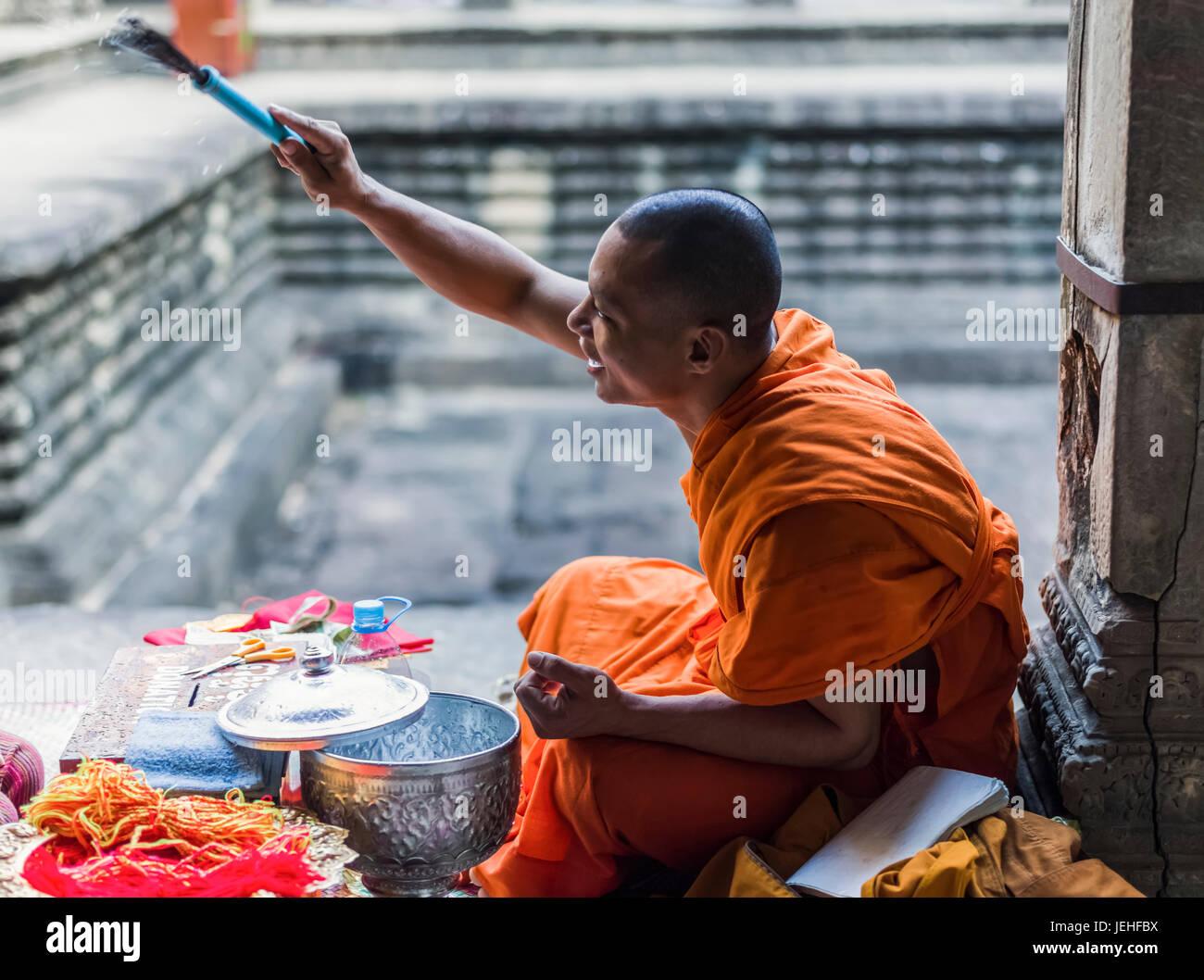 A monk sits at Angkor Wat; Krong Siem Reap, Siem Reap Province, Cambodia Stock Photo