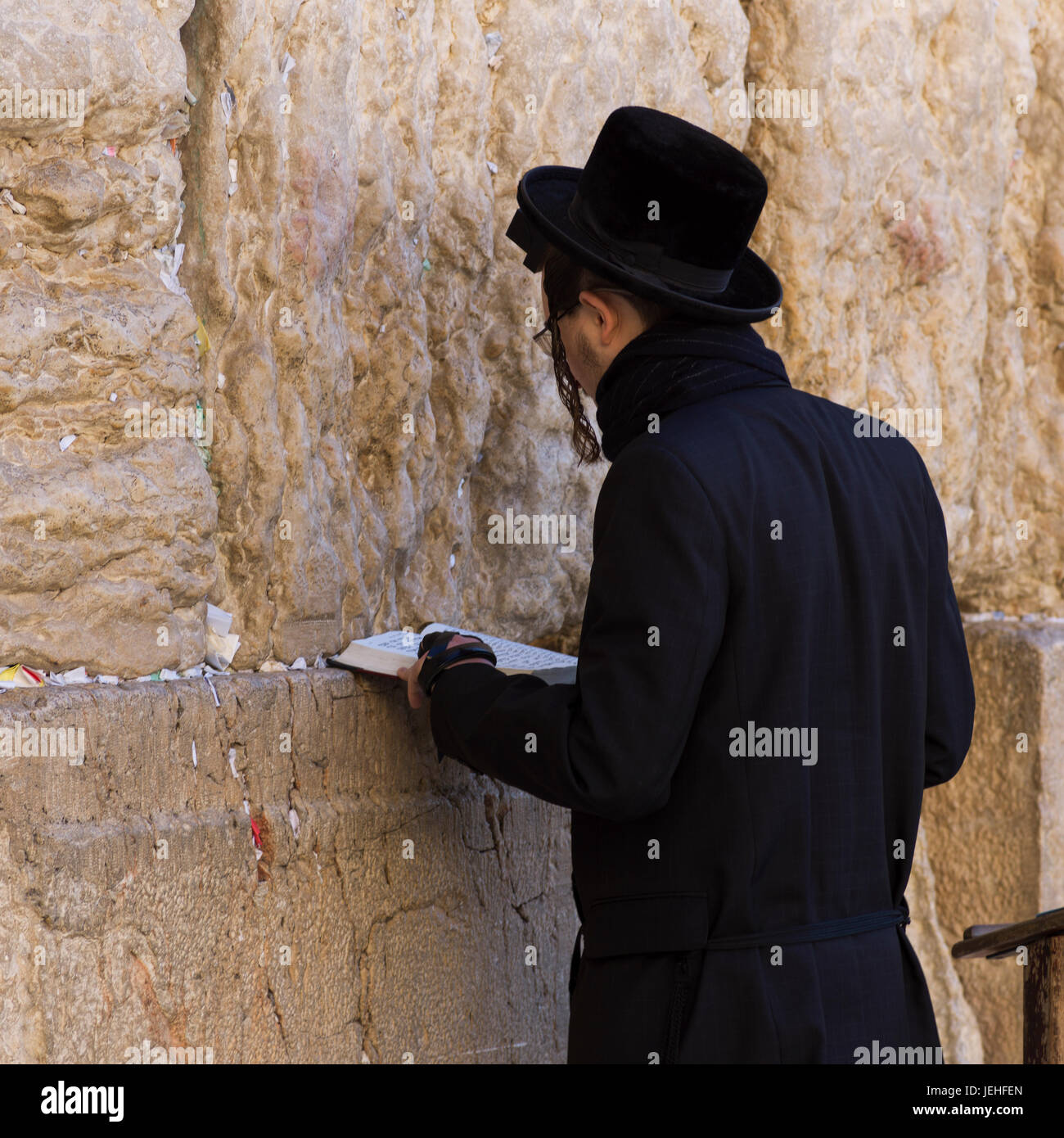 An orthodox jew standing at the Wailing Wall, old city of Jerusalem; Jerusalem, Israel - Stock Image