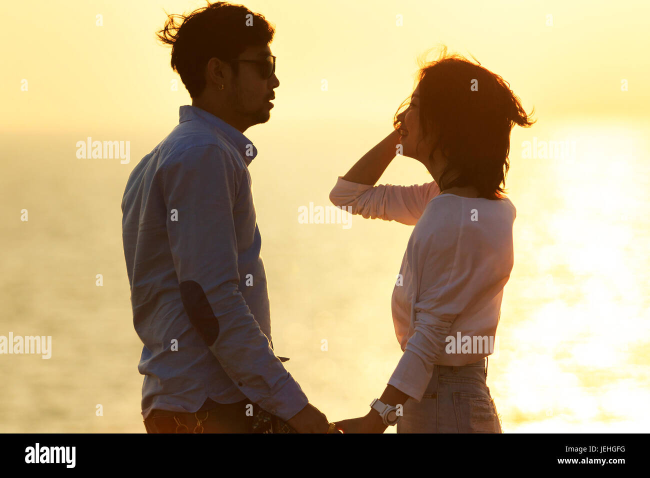 silhouette photography portrait of asian younger man and woman relaxing vacation at sea side happiness emotion against - Stock Image