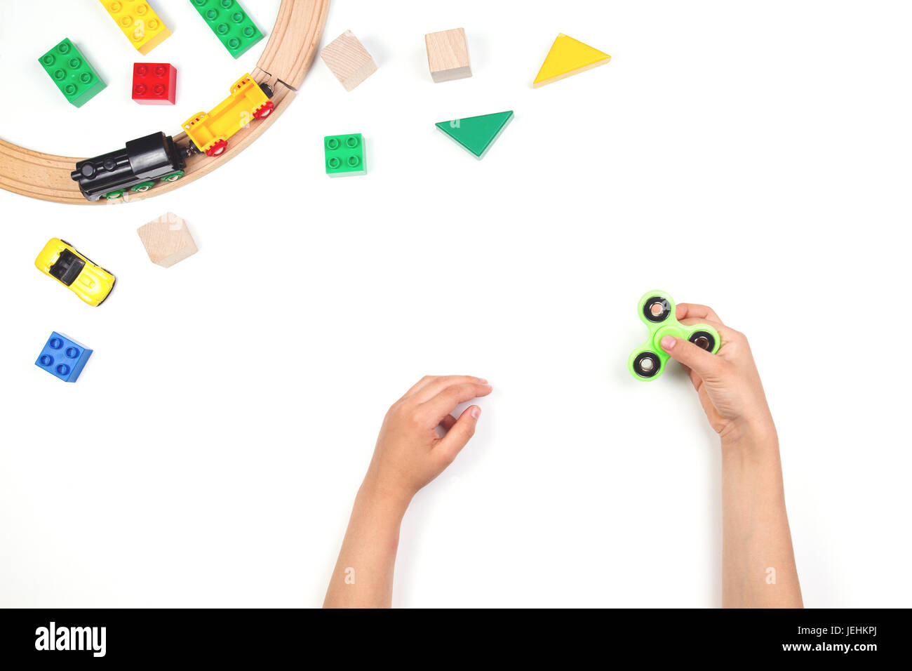 Kids hands playing with fidget spinner toy. Many colorful toys on white background. Stock Photo