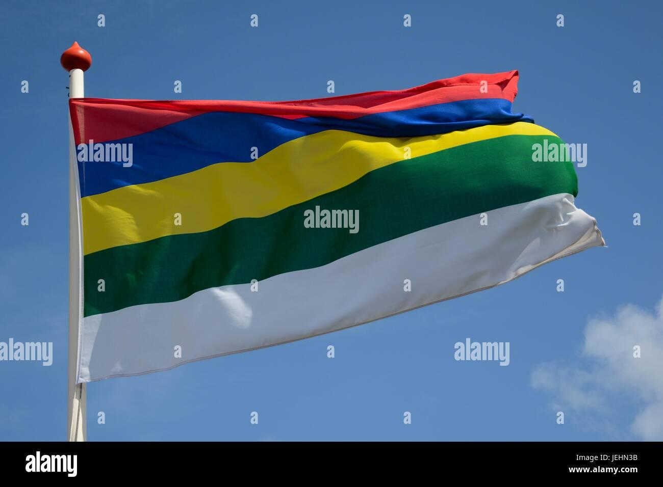 Reade wolken; Blaue lucht; Gele helmen; griên ges; Wyt sân; Dat is 't wapen fan Schylgerlân Stock Photo