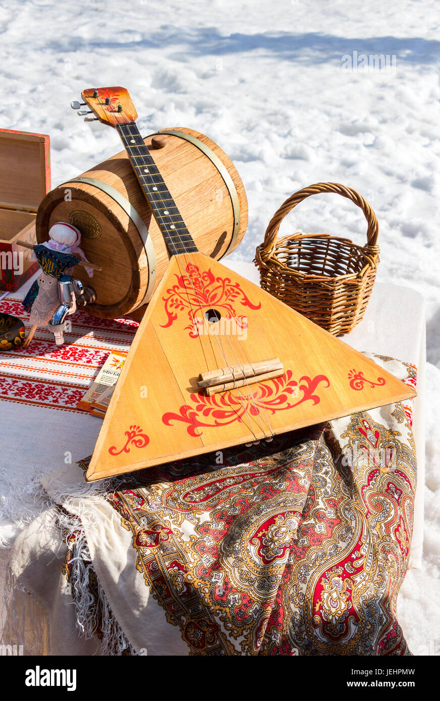 Balalaika and other products of Russian folk art over the snow background - Stock Image