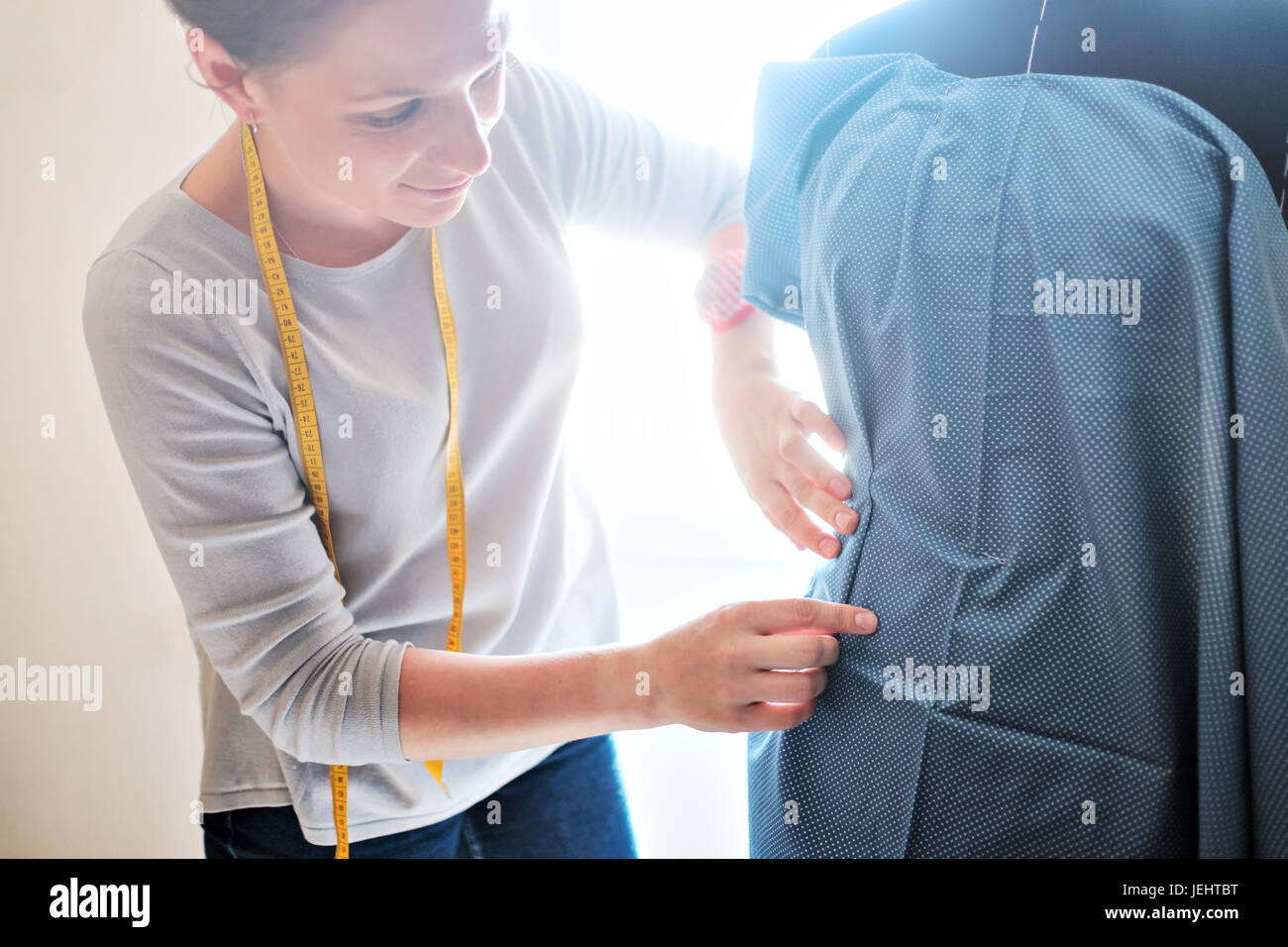 Young caucasian female fashion designer measuring a dress. - Stock Image
