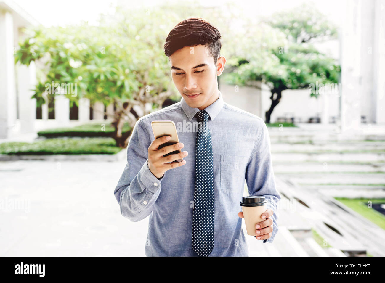 Friendly Businessman Smile with smart phone outdoor, Lifestyle of modern male to communicate or use technology in - Stock Image
