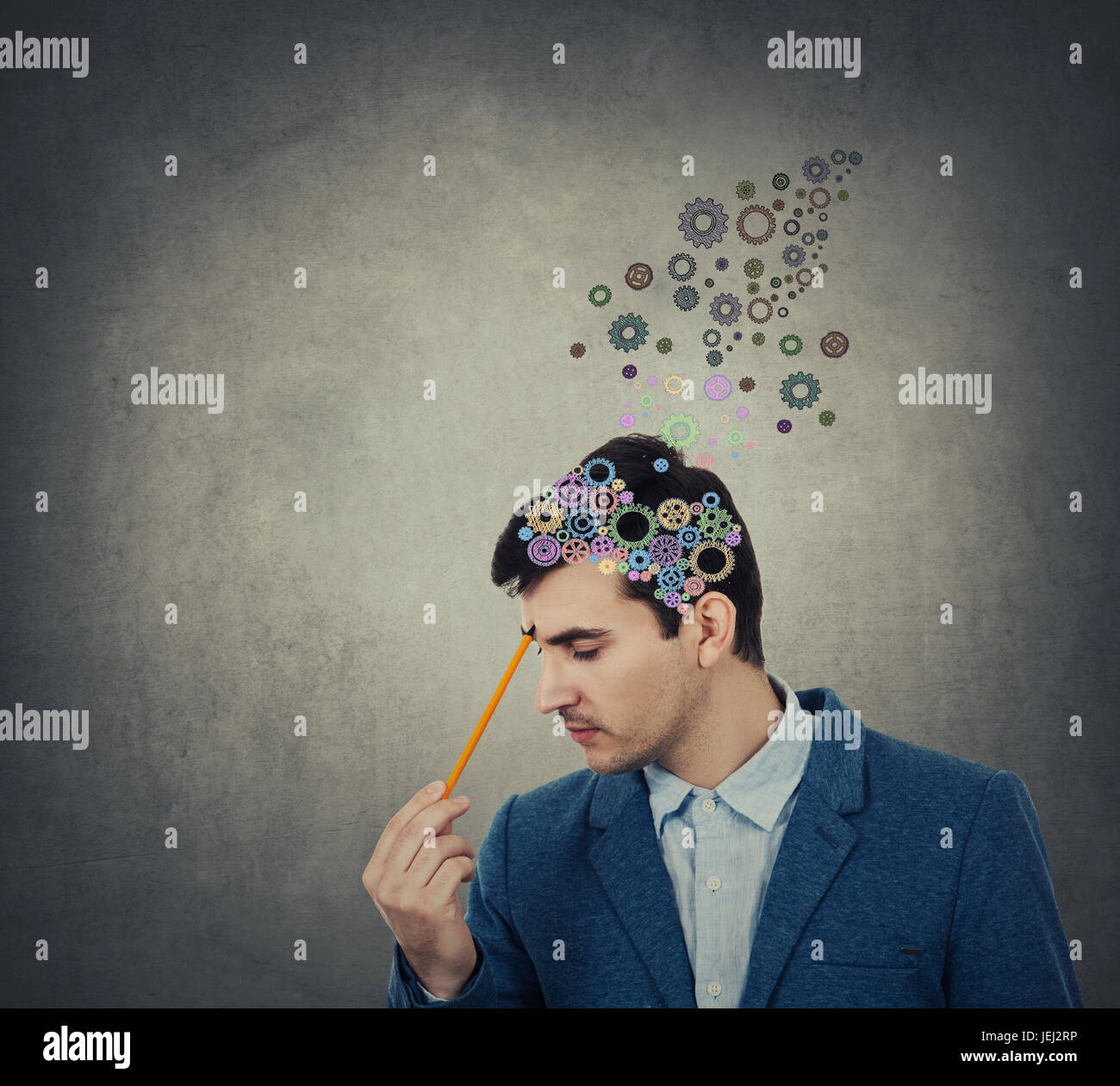 Successful businessman thinking and creating  with a pencil pointed to his head a coloruful brain made from gear - Stock Image