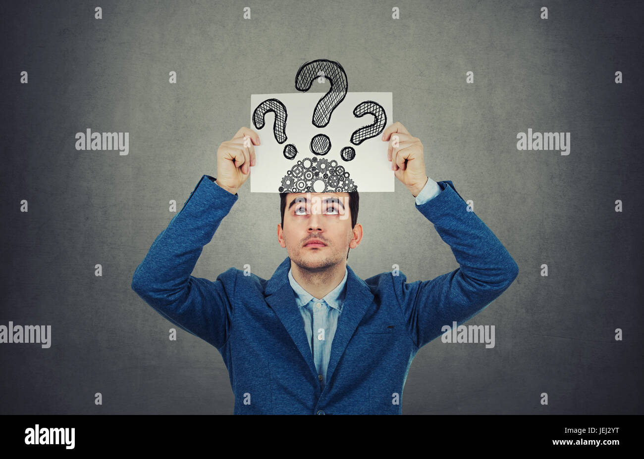Portrait of confused, thinking young businessman seeks a solution looking up, holding a paper over head with drawn - Stock Image