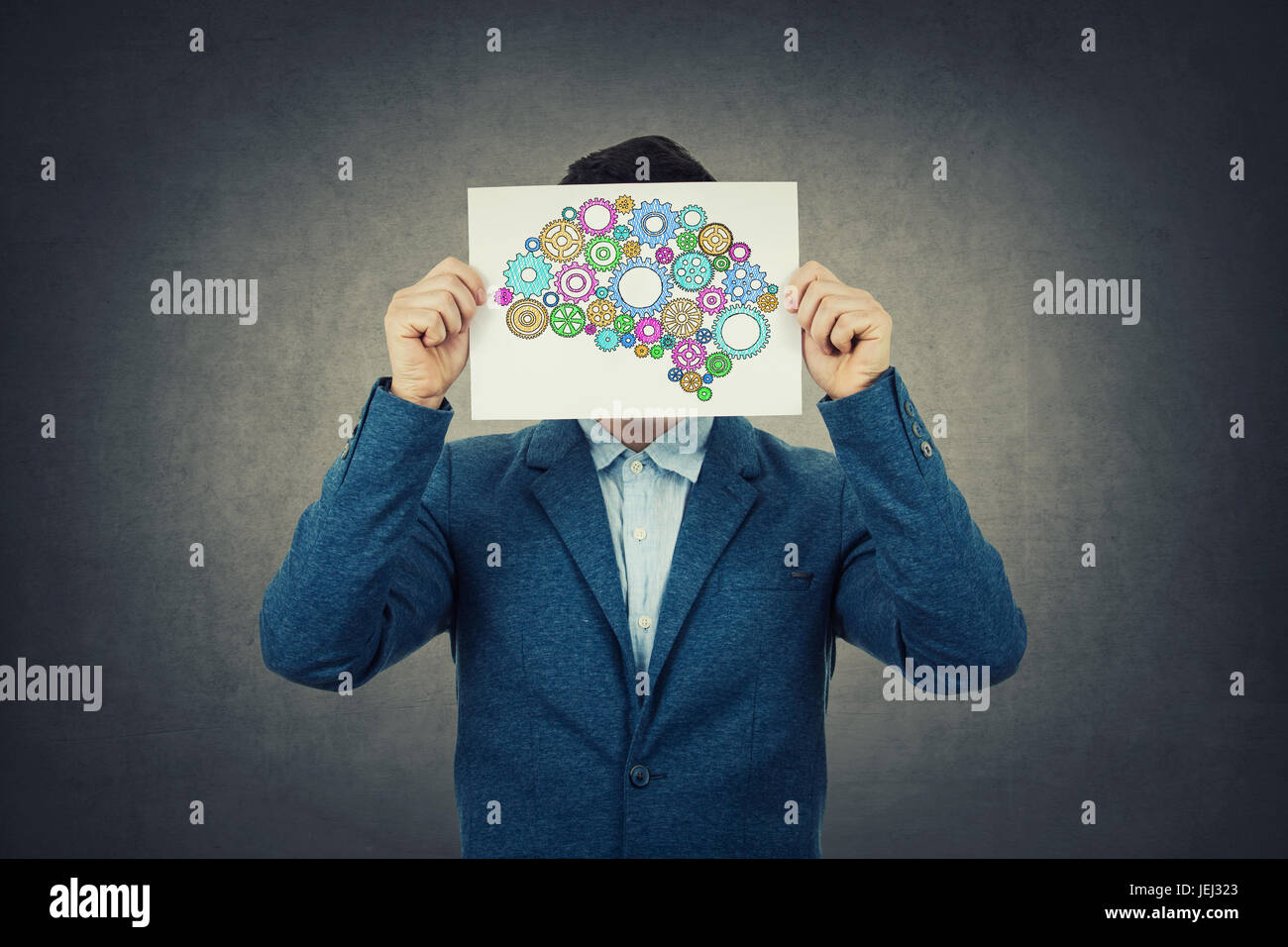 Creativity concept of a businessman covering head with a colorulful brain made from gears over his head.Idea concept. - Stock Image
