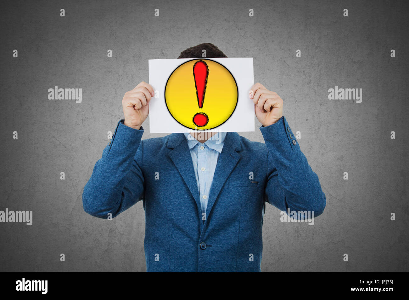 Businessman covering his face using a white paper with drawn question mark, like a mask, for hiding his identity. - Stock Image