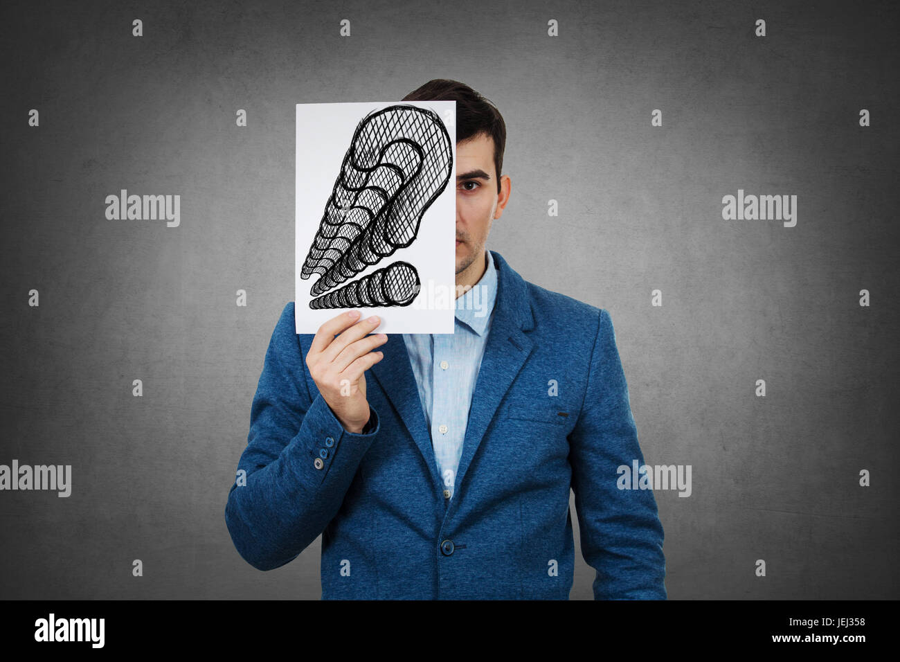 Portrait of a sad businessman, hiding half his face using a white paper drawn with questions marks.Sad student hiding - Stock Image