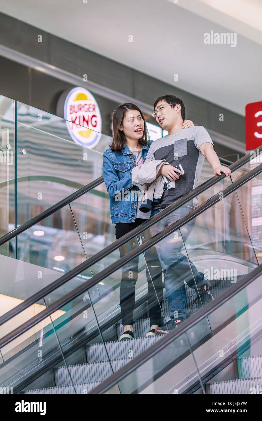 BEIJING-MAY 15, 2016. Cheerful Couple in shopping mall. China's economy, boosted by middle class wealth, undergoes - Stock Image
