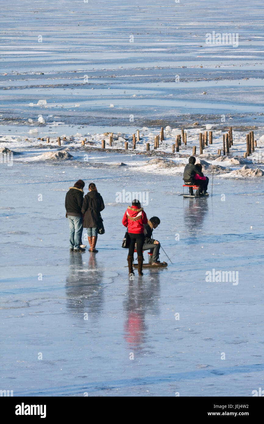 HARBIN-MARCH 7. City dwellers enjoy frozen Songhua River. Harbin is located Northeast China under influence of cold - Stock Image
