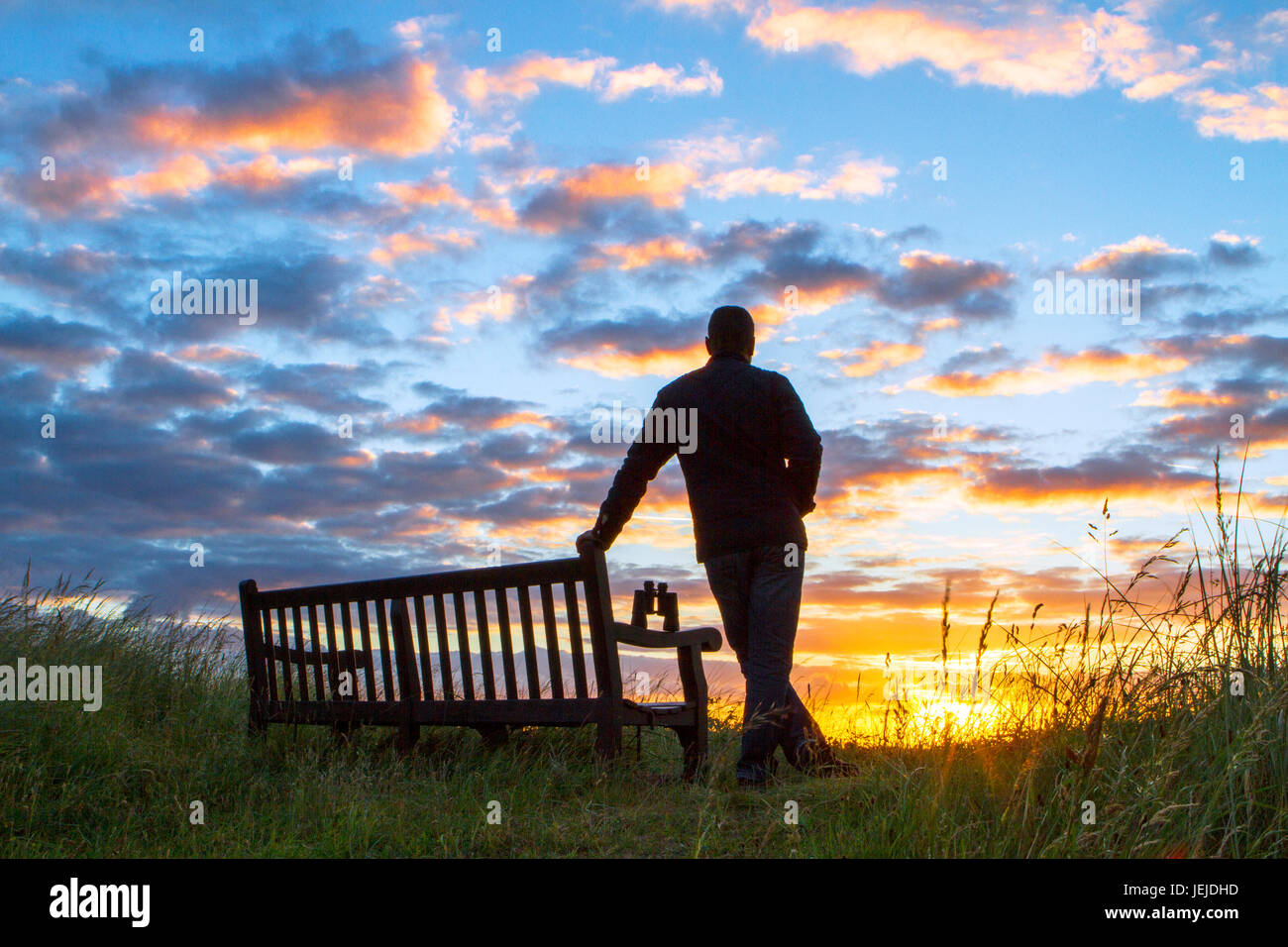 Southport, Merseyside, 26th June 2017. UK Weather. An early morning birdwatcher observes a beautiful sunrise during Stock Photo