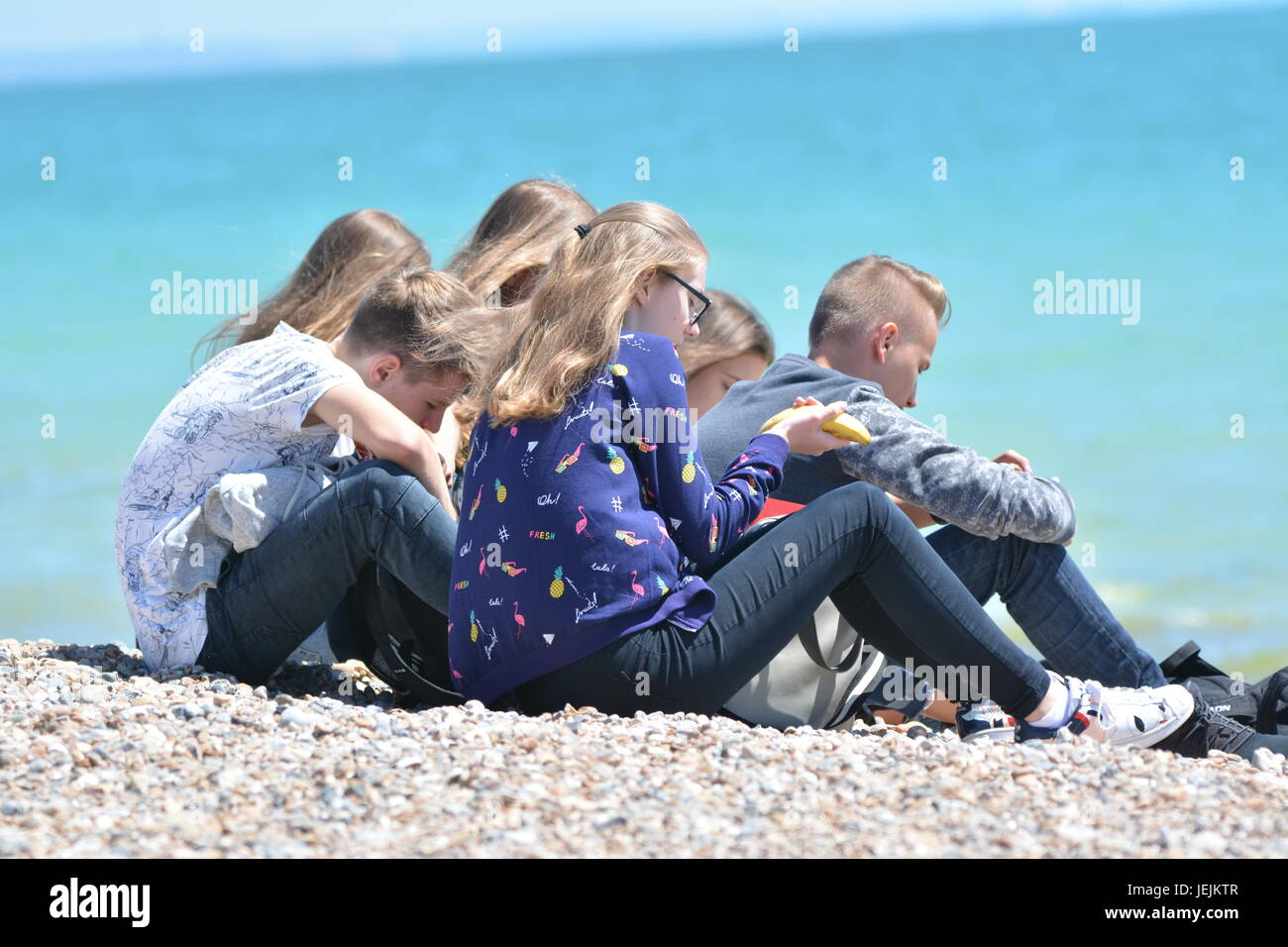 Group of young students sitting on a shingle beach on a hot day in Summer in the UK. - Stock Image