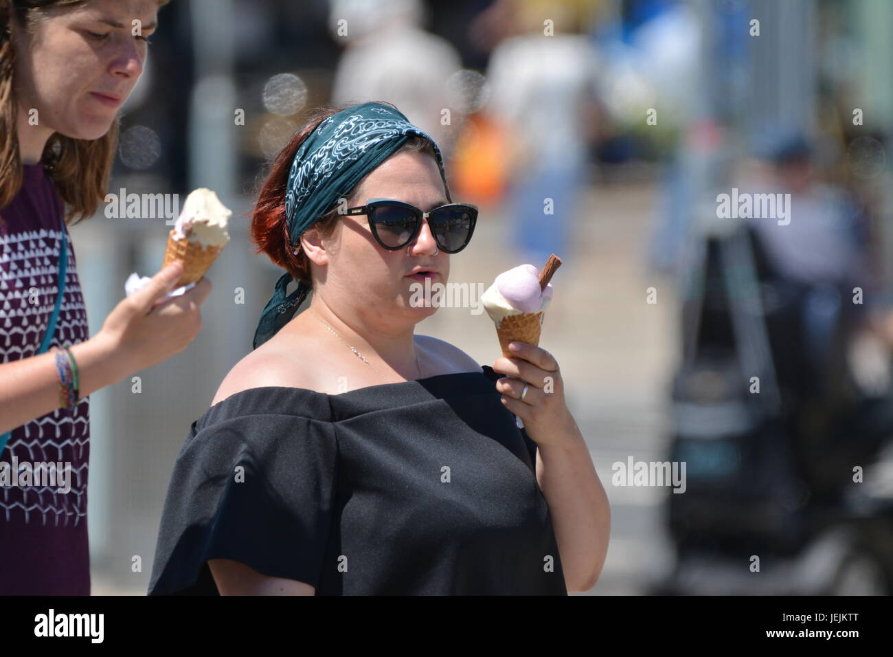 Woman eating a 99 ice cream cone on a hot day in Summer in the UK. - Stock Image