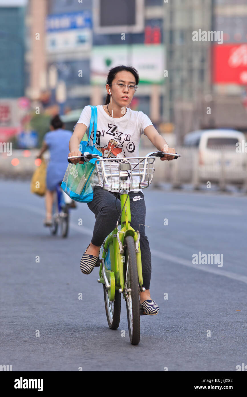 BEIJING-JULY 10, 2015. Young woman rides a public share bicycle. Bicycle sharing allow to hire on short term basis, Stock Photo