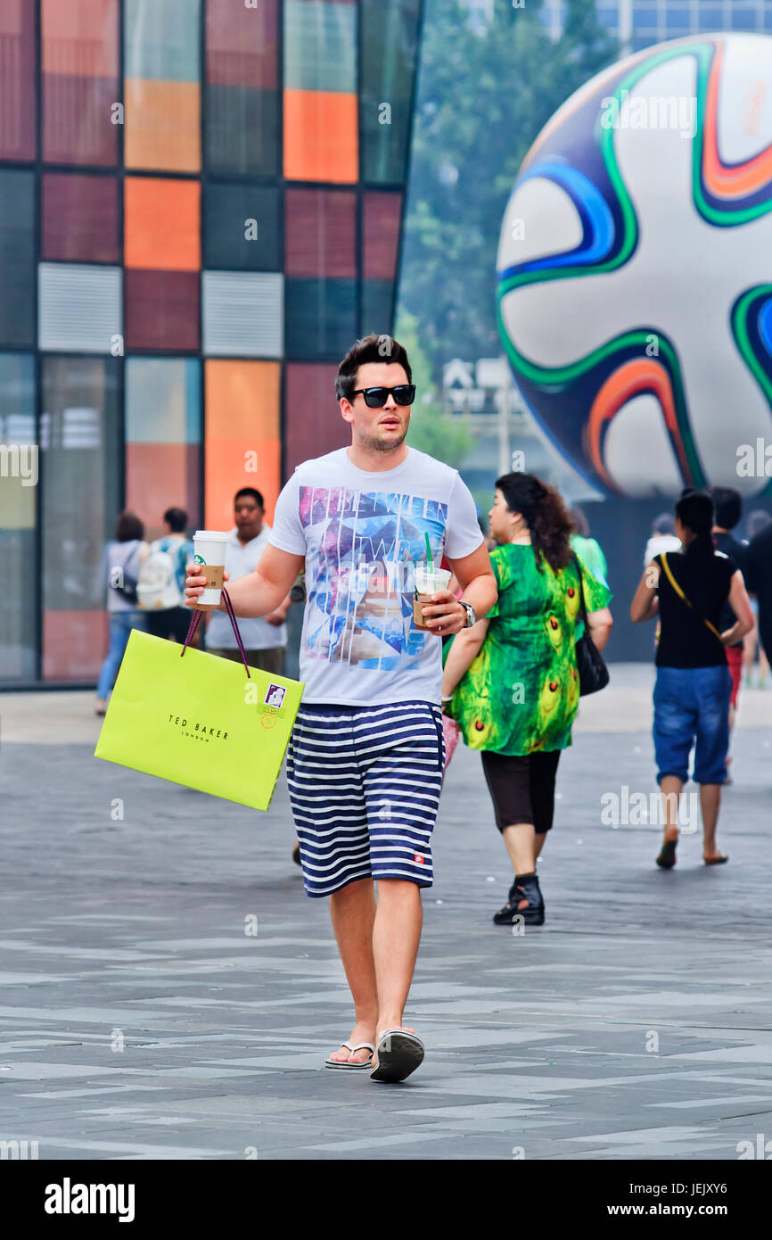 BEIJING-JUNE 25, 2014. Fashionable young man with Starbucks drinks. Chinese consumers thirst for Starbucks coffee - Stock Image