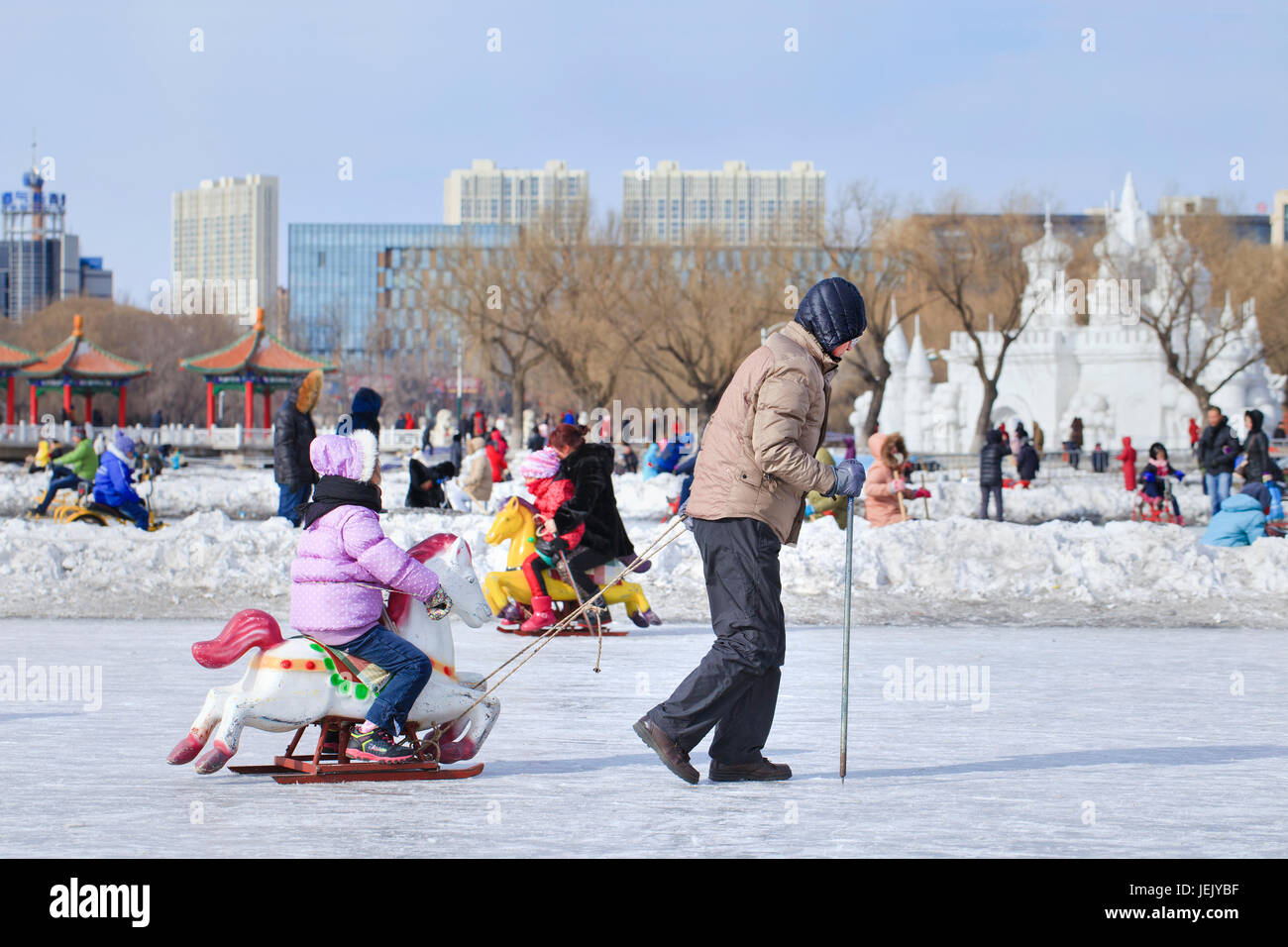CHANGCHUN – FEBR. 3, 2014. People have fun with sledging on the ice in Nanhu Park Changchun, capital of northeast - Stock Image
