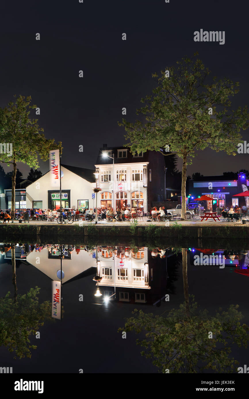 Piusharbor with café and people at night. It is a former industrial area,  near Tilburg center, developed into - Stock Image