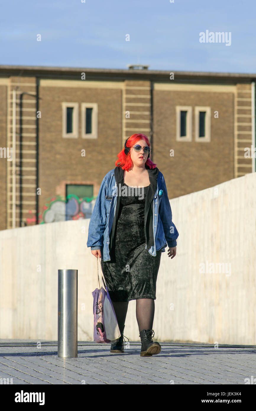 Alternative dressed girl with red hair. Alternative fashion includes specific subcultures like emo, scene, Goth, Stock Photo