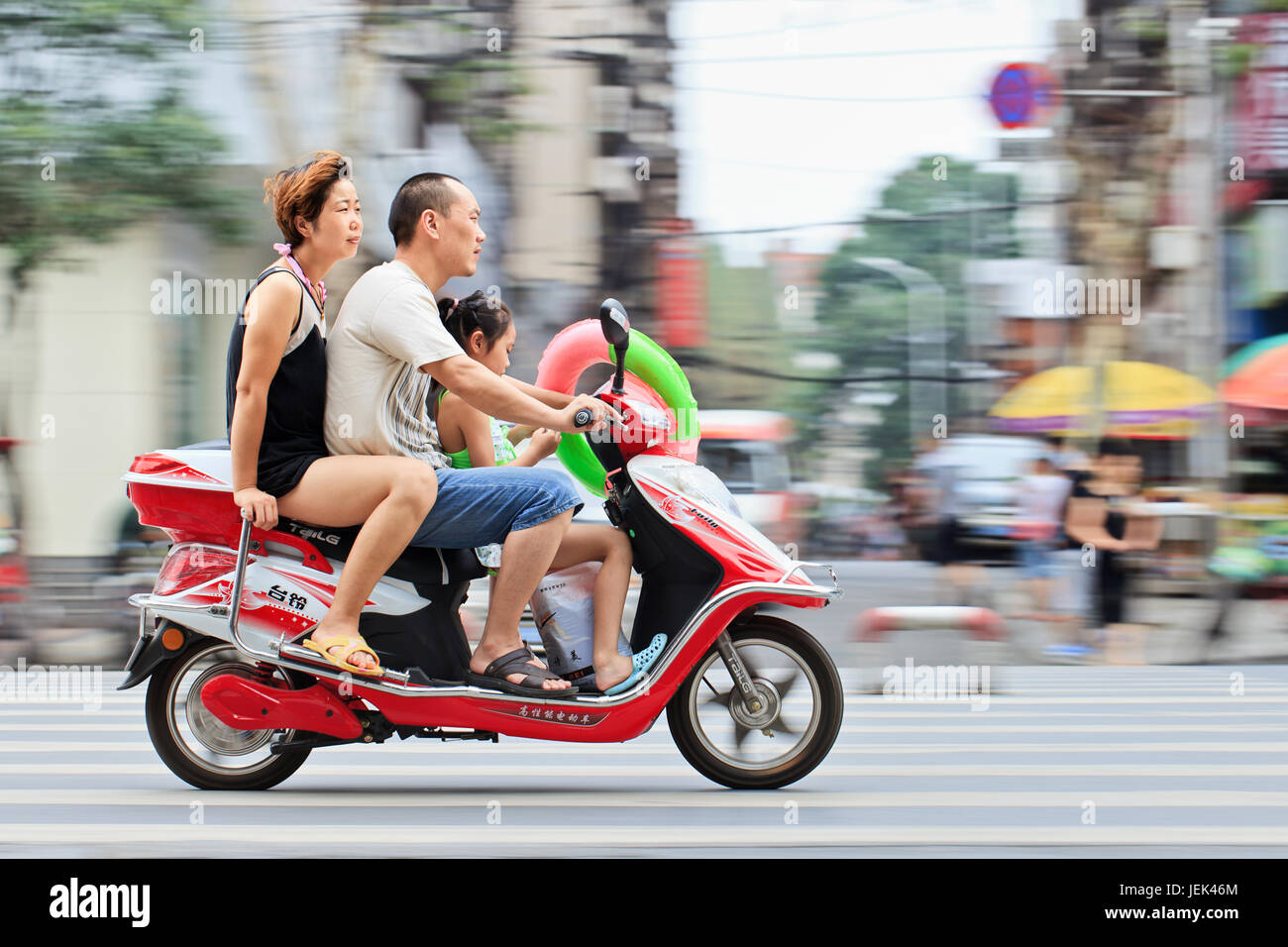 XIANG YANG-CHINA-JULY 3, 2012. Couple with their child on a scooter. China's family planning policy officially restricts - Stock Image