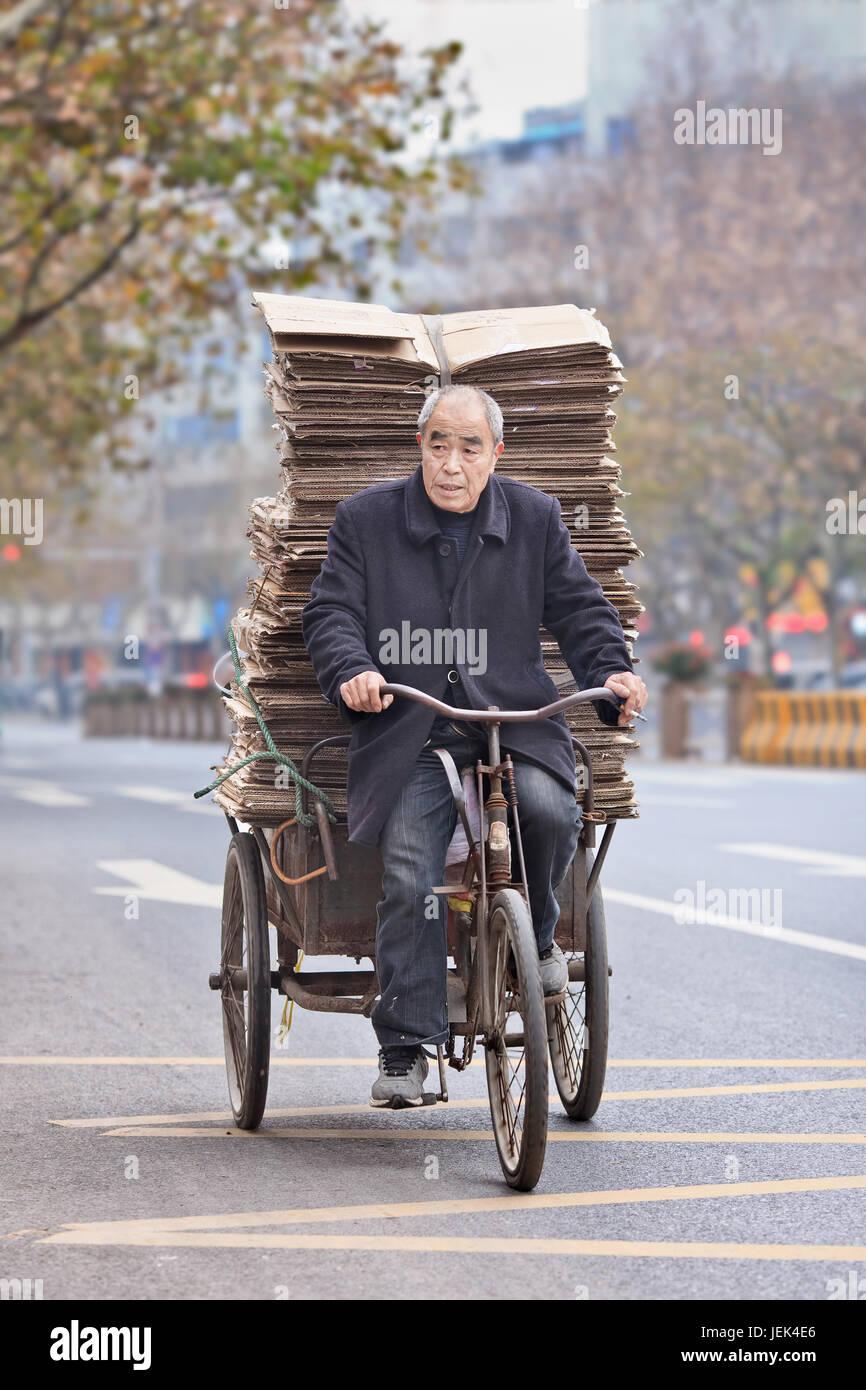 YIWU-CHINA-JAN. 8, 2016. Senior man transports cardboard on a tricycle. Elderly population of China (60 or older) - Stock Image