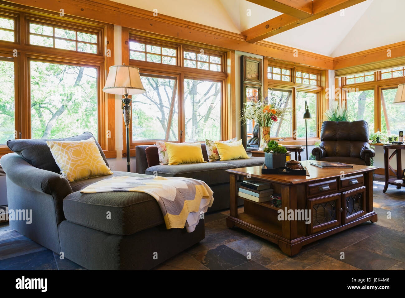 Sectional sofa and antique wooden coffee table in the new extension inside an old (circa 1740) Canadiana fieldstone - Stock Image