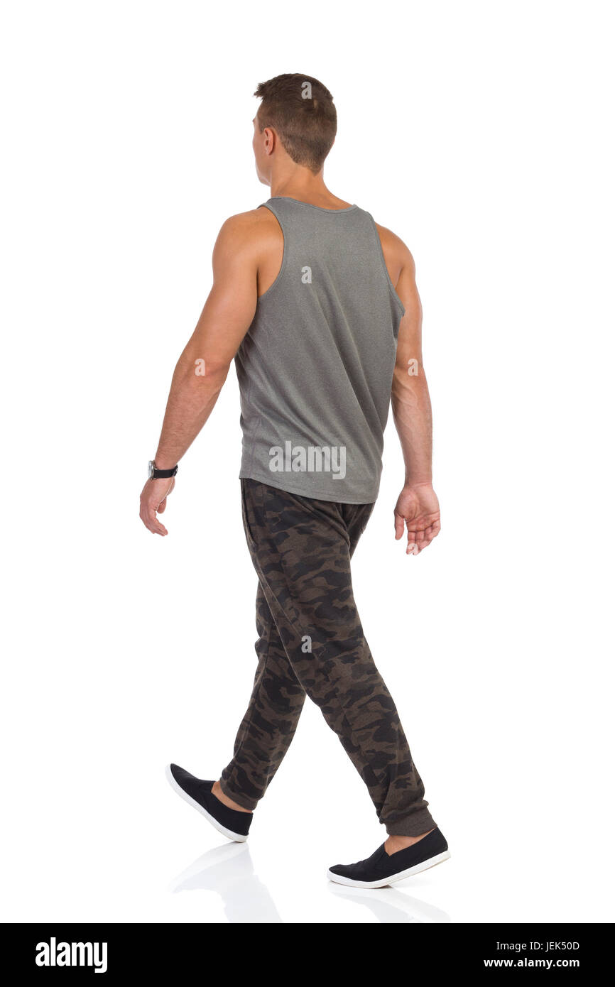 Young man walking in tracksuit pants with camo, gray tank top and black sneakers. Rear view. Full length studio - Stock Image