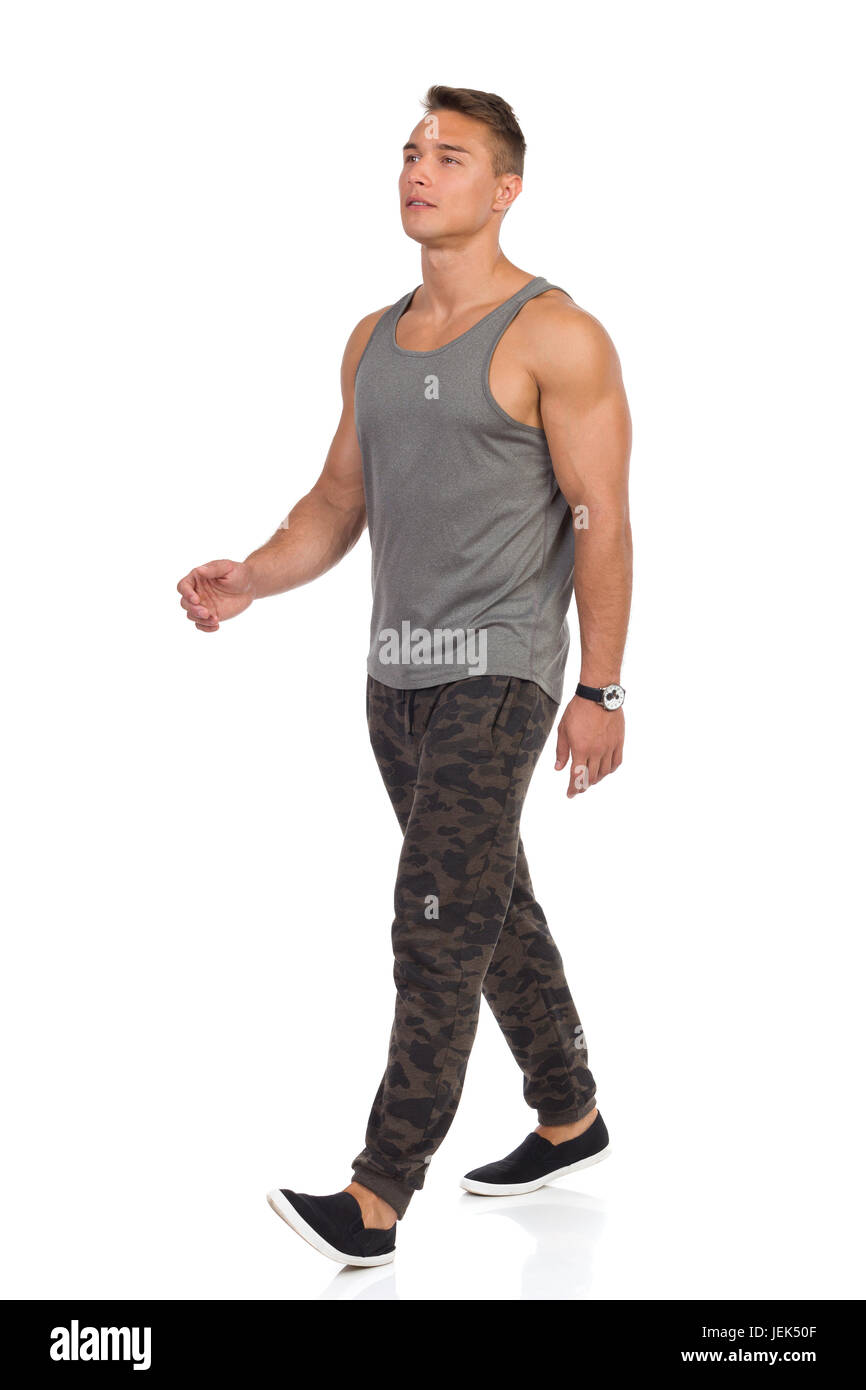 Young man walking in tracksuit pants with camo, gray tank top and black sneakers. Full length studio shot isolated - Stock Image