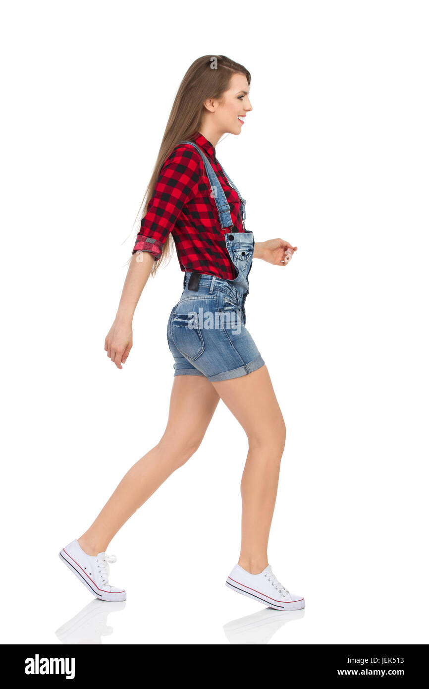 Woman in red lumberjack shirt, jeans dungarees shorts and white sneakers walking tiptoe and looking away. Side view. - Stock Image