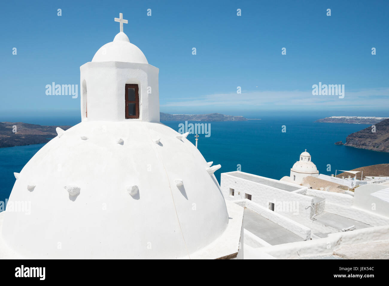 White cupola of church with Aegean sea and volcanic island in background, Santorini, Greece Stock Photo