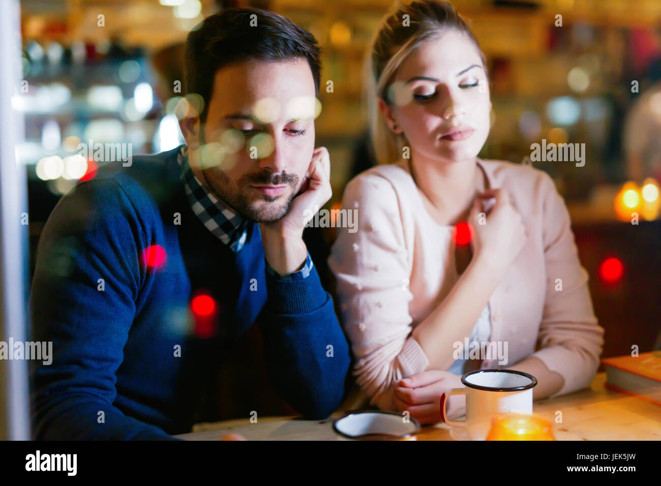 Sad couple having conflict and relationship problems sitting in bar - Stock Image
