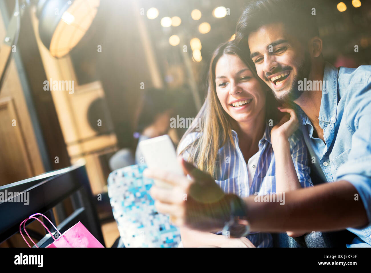 Young attractive cheerful couple on date in coffee shop - Stock Image