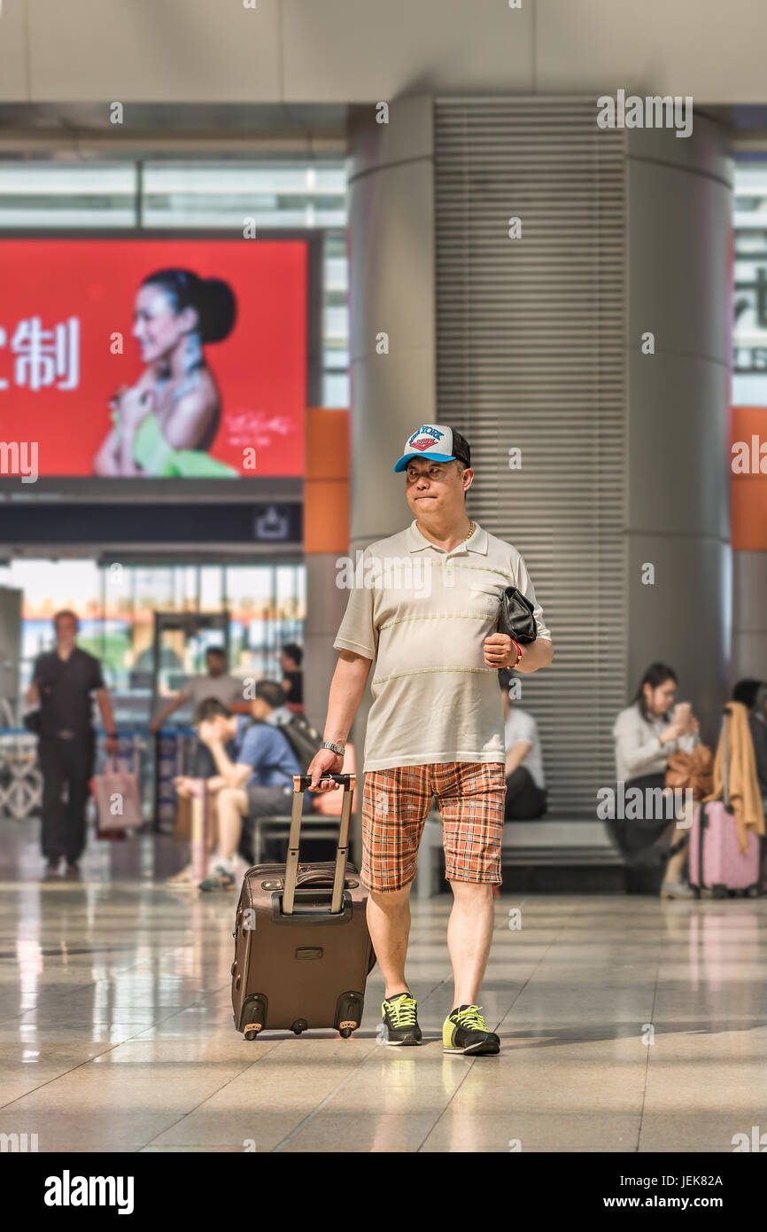 BEIJING-MAY 21, 2016. Summerly dressed man at Beijing Railway Station South, city's largest station and one - Stock Image