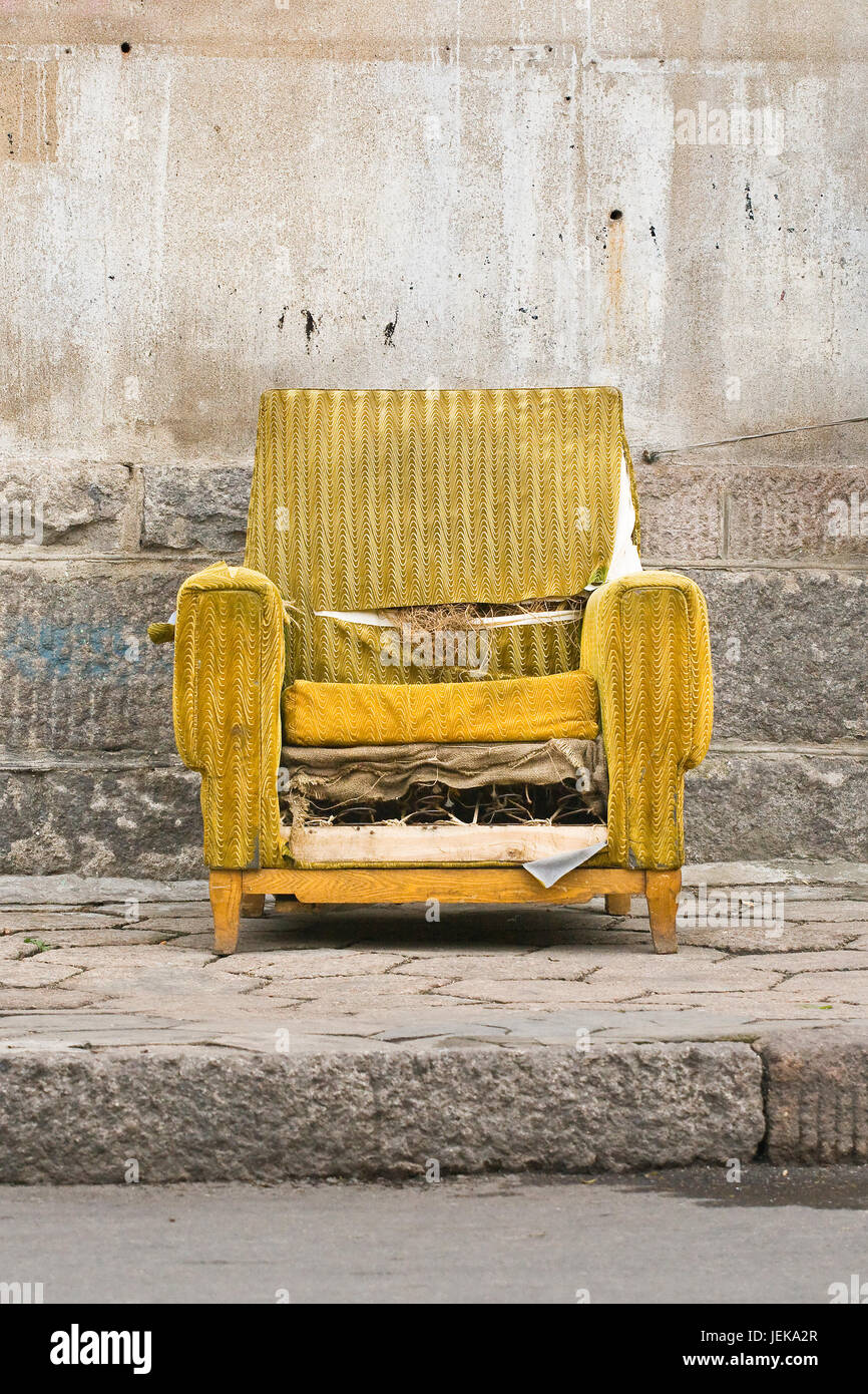 Old worn out yellow chair against a stone wall Stock Photo
