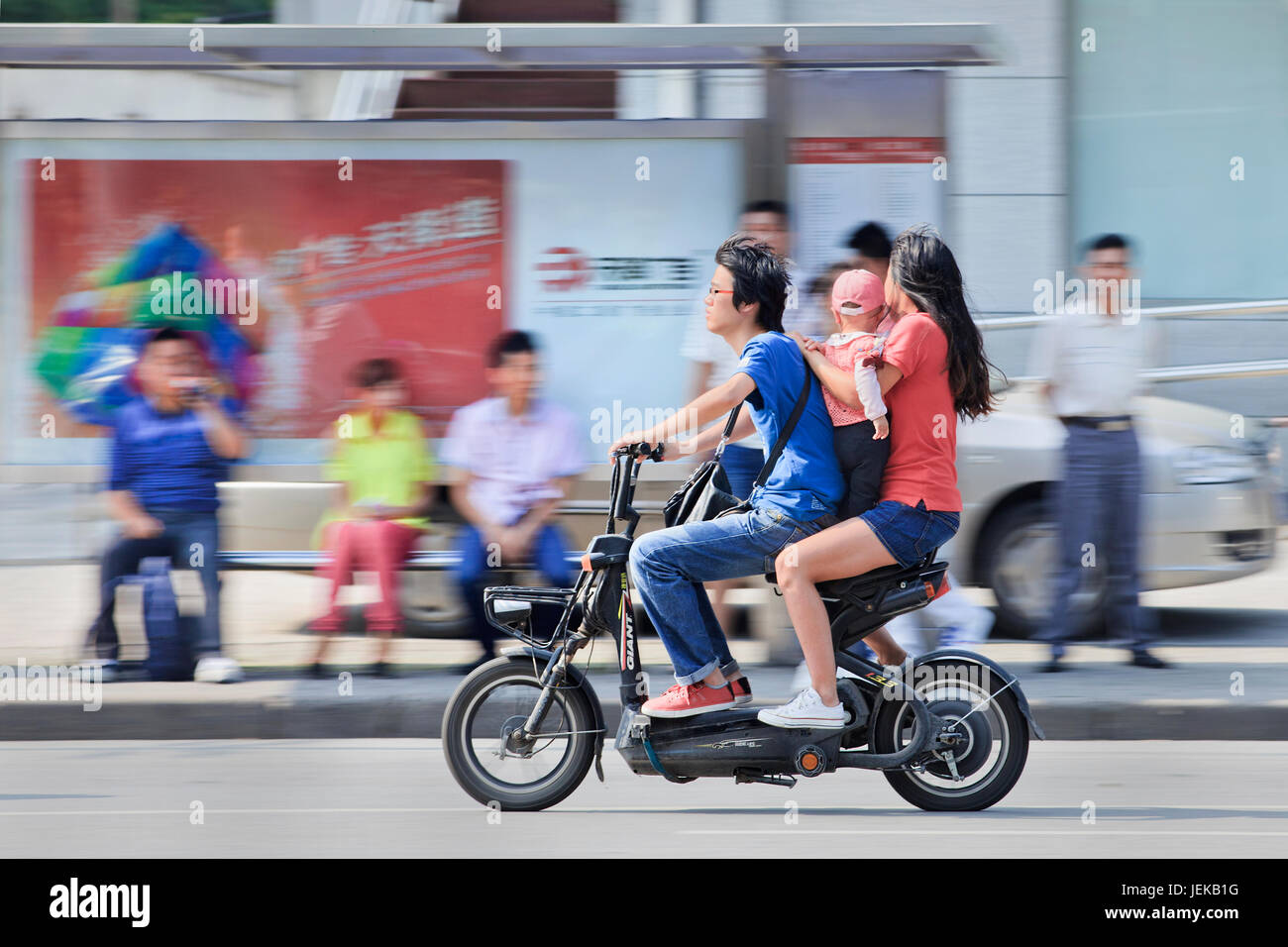 Couple with child on electric bike. China's government family planning policy officially restricts married, urban - Stock Image