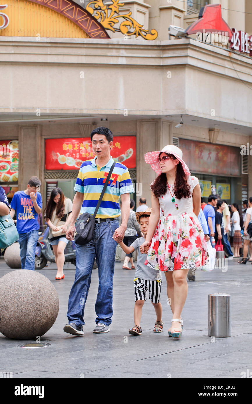 Couple with child downtown. With a population of over 1.3 billion and dwindling natural resources, China has one - Stock Image