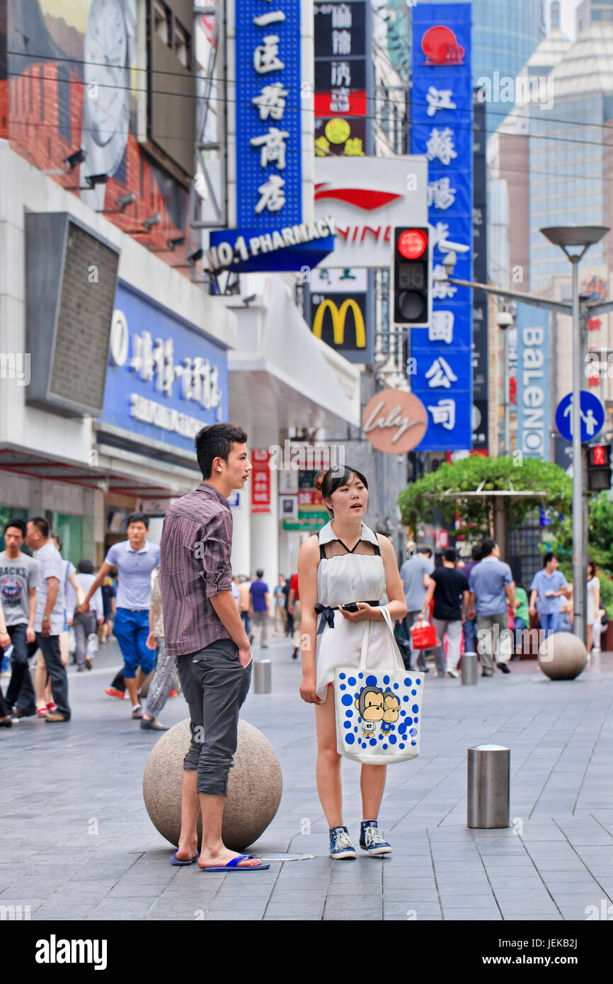 Young Chinese couple in Nanjing East Road. It is China's 3.4-mile long premier shopping street, a must-see metropolitan - Stock Image